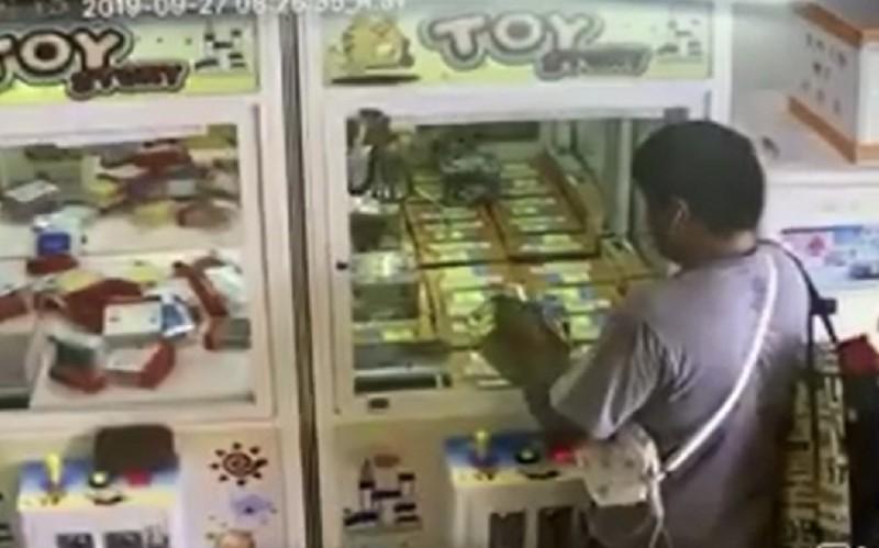 男子利用強力磁鐵竊取娃娃機內的高價耳機,過程被監視器拍下。(圖擷取自臉書社團「埔里人通通+近來)