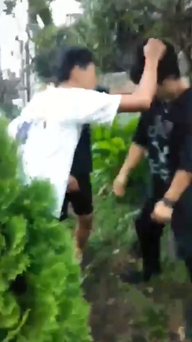 一名穿黑色T恤的少年,遭對方拳腳相向,跪跪地求饒頻說:「拍謝啦!」、「各位哥哥對不起!」仍被對方圍毆,相當兇狠。(記者林嘉東翻攝)