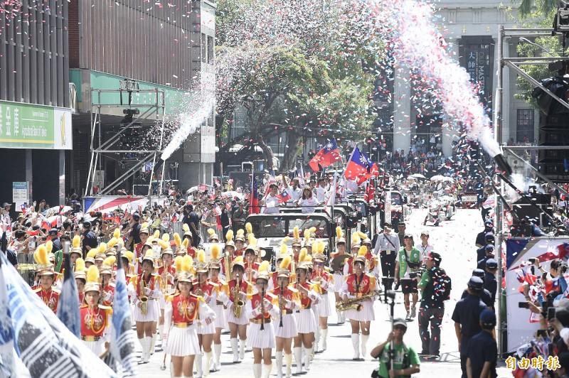 台灣英雄隊伍進入館前路,兩旁噴出紙花,民眾揮舞國旗歡迎車隊。(記者陳志曲攝)