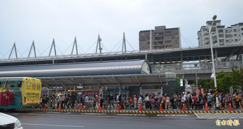 等著搭乘接駁車前往國慶煙火會場的民眾大排長龍。(記者李立法攝)