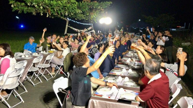 在嘉義縣鹿草鄉舉辦的田野晚宴,民眾在月光下享用美食。(記者林宜樟翻攝)