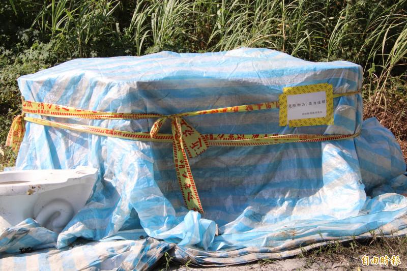 新竹檢警會同環保署等專業單位,把被偷丟在鳳山溪畔、7桶疑似含有高濃度「化骨水」成份的有害事業性混合廢液桶,就地做好防範措施後封存,且張貼佈告警示。(記者黃美珠攝)