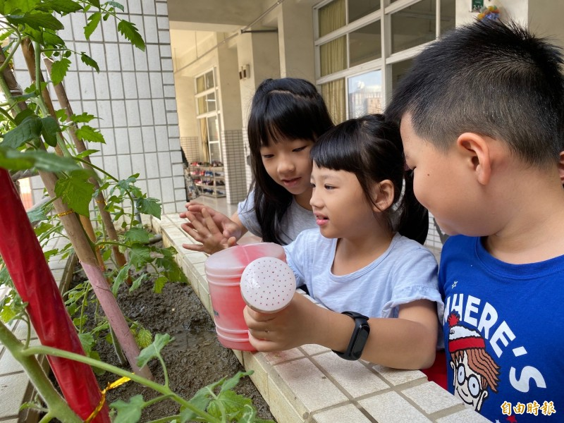 學童為陽台作物澆水。(記者黃旭磊攝)