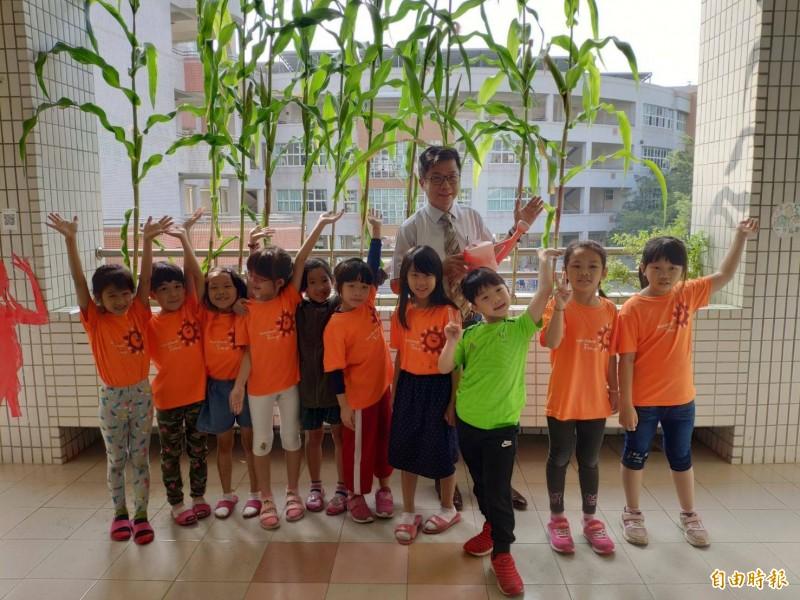 新上國小校長王彥嵓(後排中)與學童一起照顧玉米田。(記者黃旭磊攝)