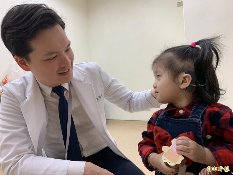 醫師溫惟昇為簡小妹雙耳裝上電子耳,恢復聽力,語言能力追上同齡孩子。(記者蔡淑媛攝)
