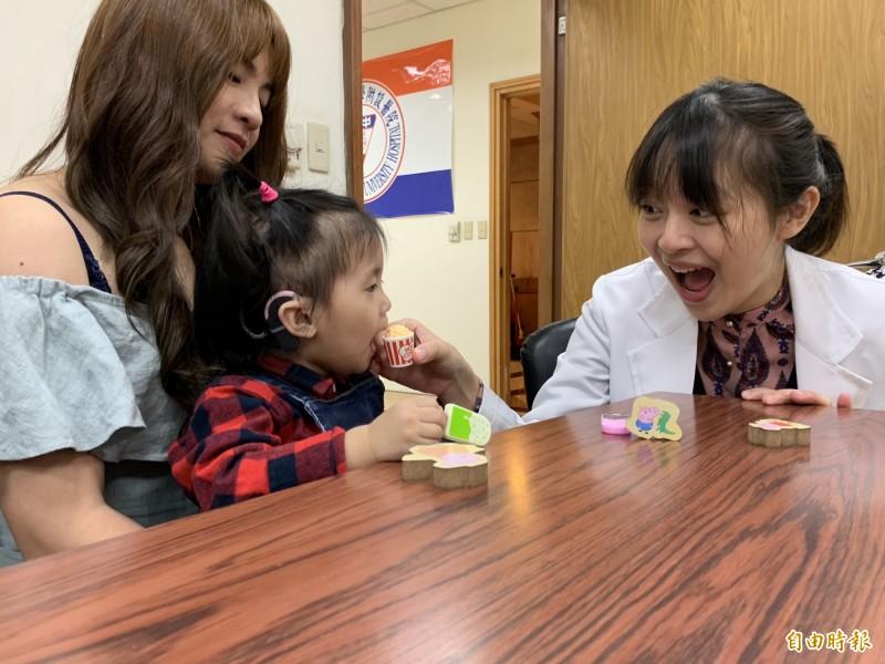 簡小妹裝上電子耳恢復聽力後,接受聽能創建訓練,了解聽到的訊息,跟著聽力師沈婉婷做動作。(記者蔡淑媛攝)