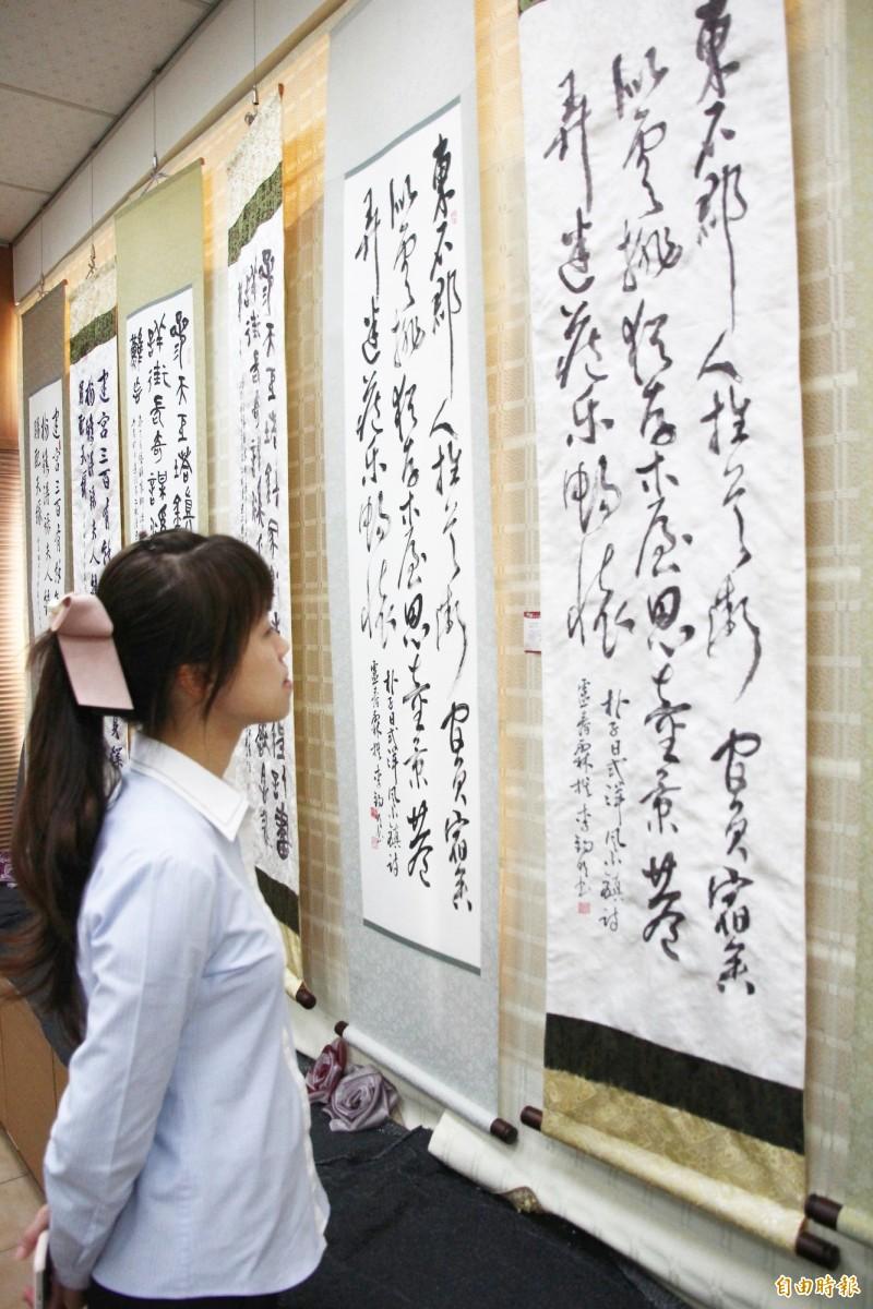 朴子市長吳品叡欣賞手工刺繡的書法字作品和書法作品,讚嘆不已。(記者林宜樟攝)