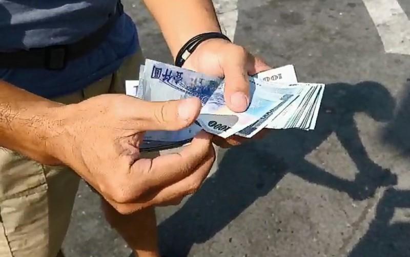鈔票飛滿地,鄭姓男子在警方見證下,當場計數拾獲金額。(記者楊金城翻翻攝)