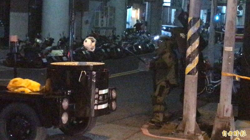 防爆人員緩步小心翼翼,用防爆夾夾起疑似嫌犯扔下的不明物體,放入防爆箱內運離現場。(記者黃良傑攝)