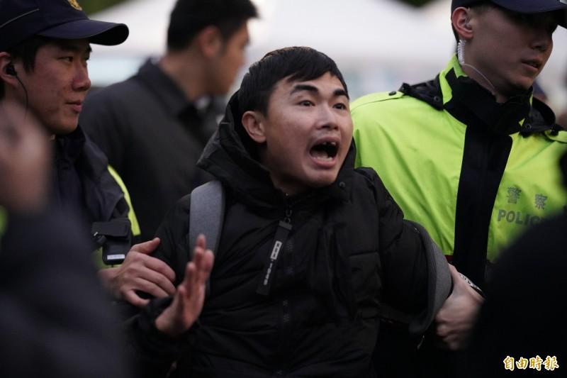「吃屎哥」游兆霖在總統府前元旦升旗典禮上高呼「韓國瑜是騙子」等語,遭警方強制抬離。(記者黃欣柏攝)