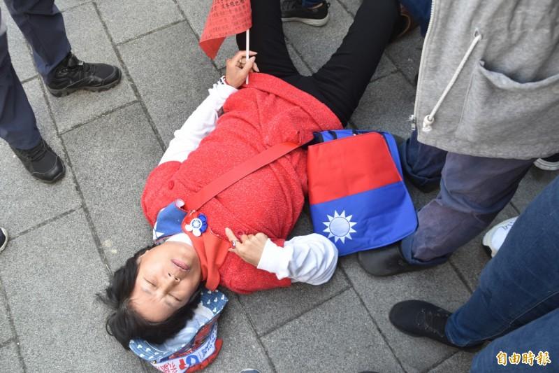1名女韓粉亂入表示遭迫害,躺在地上要求向韓國瑜陳情,結果引來其他韓粉不滿,大力推她一把,叫她閉嘴!(記者蘇福男攝)