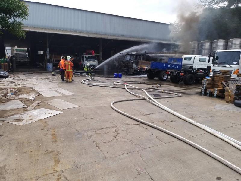 消防局救難人員到場後,立刻對起火的油罐車布水線滅火。(記者陳恩惠翻攝)