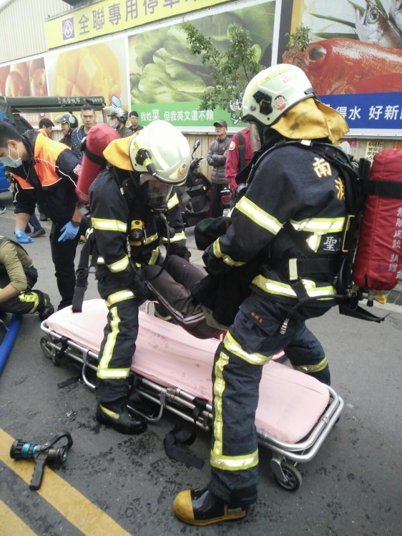 消防隊員於民宅2樓救出火災受困民眾,有吸入性嗆傷,現場給予氧氣治療後進一步送醫救治。(南投縣政府消防局提供)