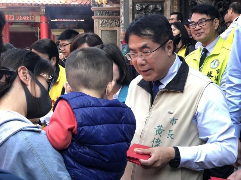 台南市長黃偉哲於小年夜白天到寺廟發送市府開運小紅包給排隊信眾、親子們。(記者王俊忠翻攝)