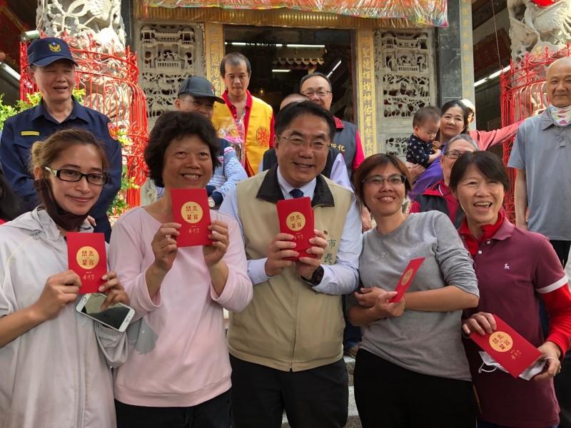 台南市長黃偉哲(前排右三)於小年夜白天到寺廟發送市府開運小紅包給排隊信眾、親子們。(記者王俊忠翻攝)