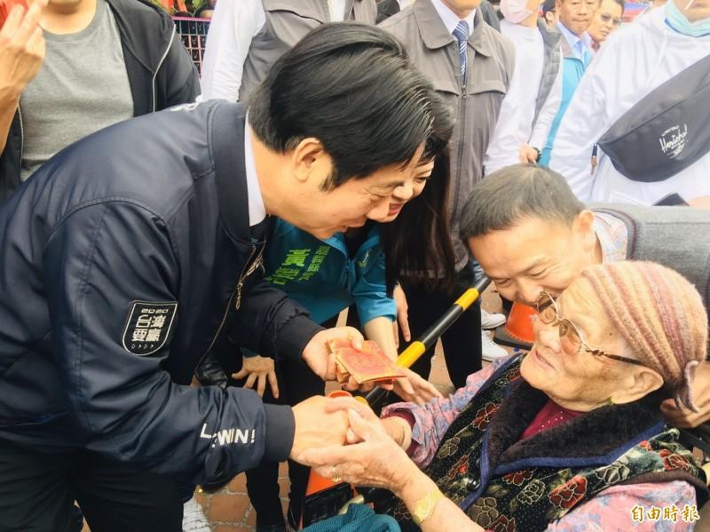 準副總統賴清德對坐著輪椅的阿婆噓寒問暖,逗著老人家笑呵呵。(記者蔡宗勳攝)