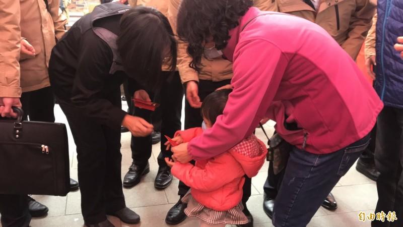 面對小小孩排隊來索福袋,小英總統(左)親切彎低了身且放慢發送的速度,甚至多寒暄幾句。(記者黃美珠攝)