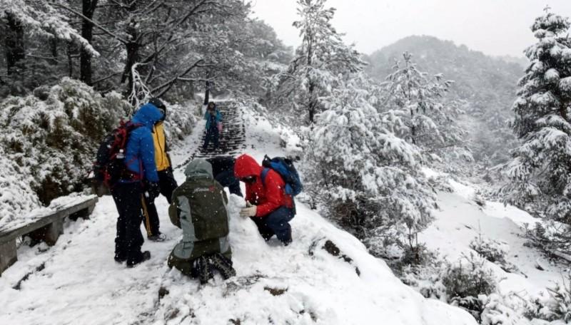 玉山因寒流下大雪,令山友驚喜,也玩起堆雪人、雪花的遊戲。(記者謝介裕翻攝)