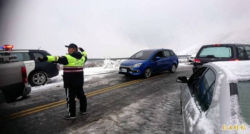 合歡山湧現賞雪人、車潮,警方進行交通指揮疏導情形。 (記者謝介裕攝)