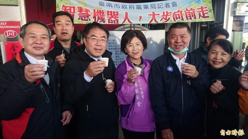市長黃偉哲(前左二)參訪佳里梅桂牧場的智慧擠乳機,並大讚牛乳好喝。(記者楊金城攝)