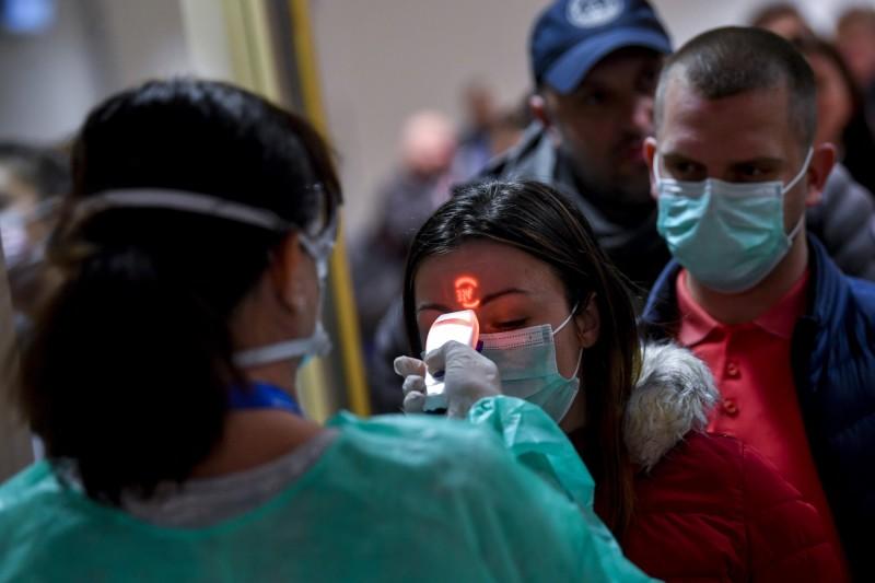 美國哈佛大學教授利普西奇預測,在接下來一年內,全球恐有70%人口感染武漢肺炎。圖為匈牙利機場人員檢測旅客體溫。(歐新社檔案照)