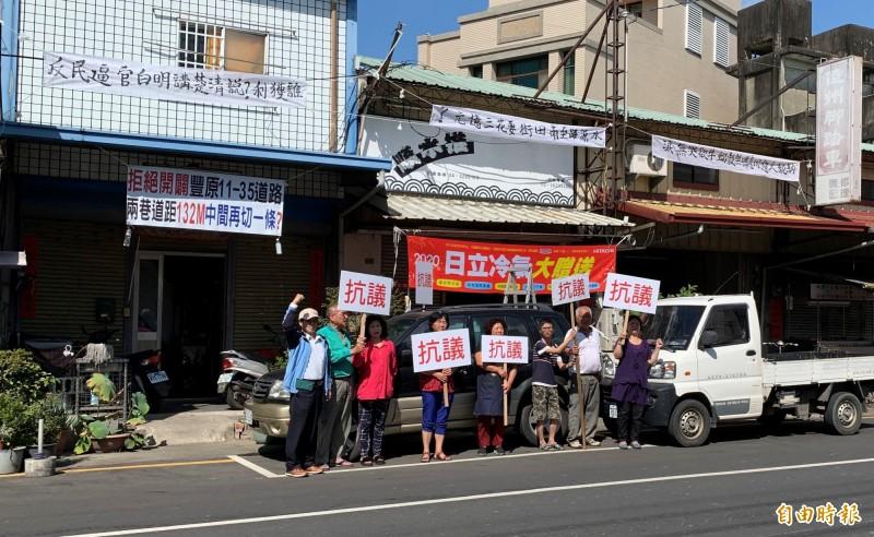 市府有意開闢豐原區「水源路11-35號道路」,反對民眾在住家懸掛白布條及舉牌抗議。(記者歐素美攝)