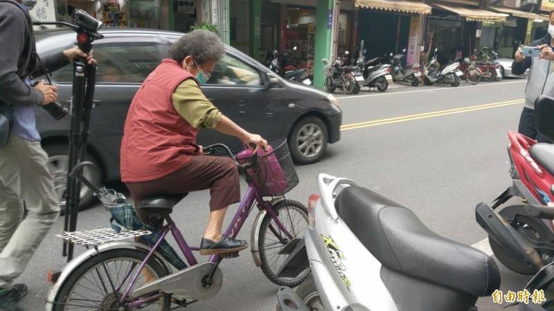 何姓婦人捐完款項後,馬上騎腳踏車離去。(記者張議晨攝)