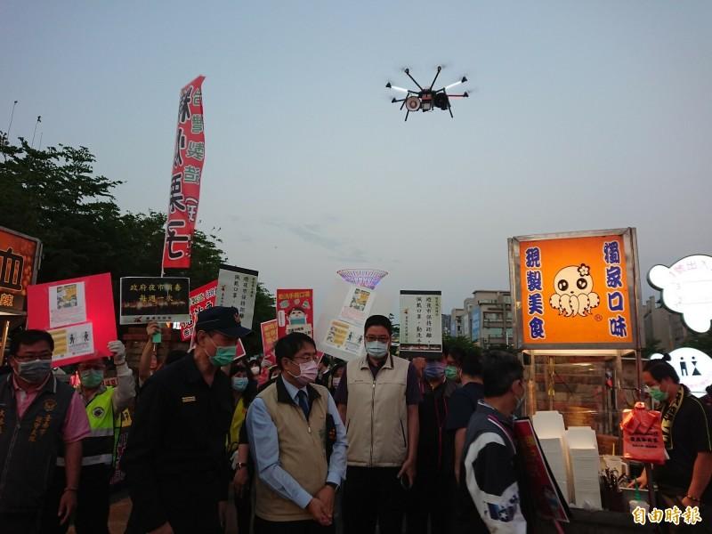 台南市長黃偉哲配合中央防疫,4日到花園夜市宣導防疫觀念,市府並出動空拍機架著「大聲公」宣導。(記者洪瑞琴攝)