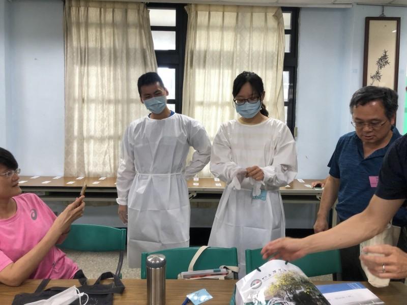 隔離考場的監考員穿上隔離衣等防疫裝備進行監考。(記者詹士弘翻攝)