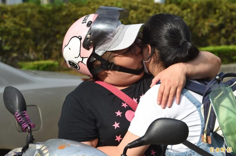 無法進場陪考的家長送上擁抱、親吻祝福。(記者劉信德攝)