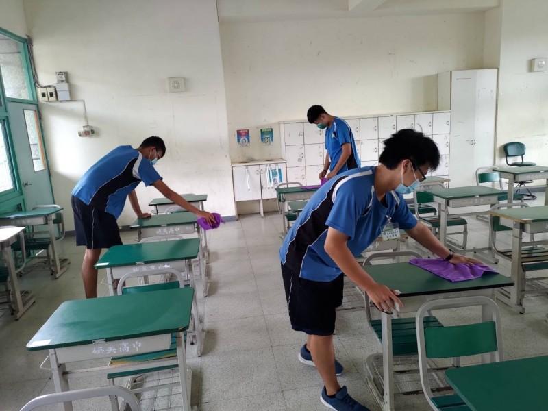 考場服務隊學生協助桌椅消毒。(教育局提供攝)