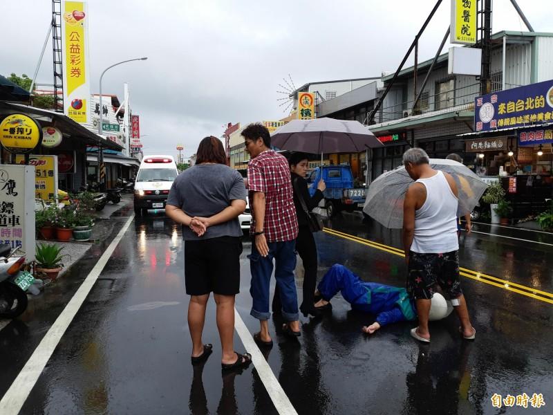 老婦騎機車車禍,倒地不起,路人在雨中為她撐傘。(記者黃明堂攝)