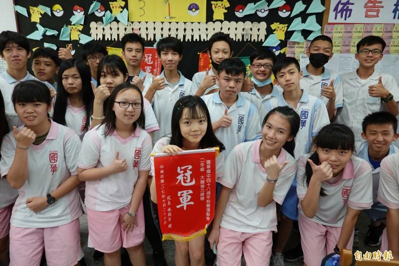張詠欣(中拿冠軍錦旗者)拿下宜蘭縣國中教育會考最高分,班上同學為她熱烈歡呼。(記者江志雄攝)