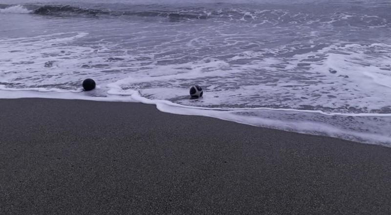 在台東市馬當海邊一起玩浪的兩顆籃球。(記者黃明堂翻攝)