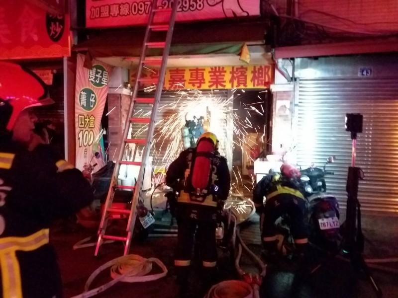 台中太平中山路一間檳榔攤今天凌晨起火,消防人員獲報到場以電鋸破壞鐵捲門搶救。(記者陳建志翻攝)
