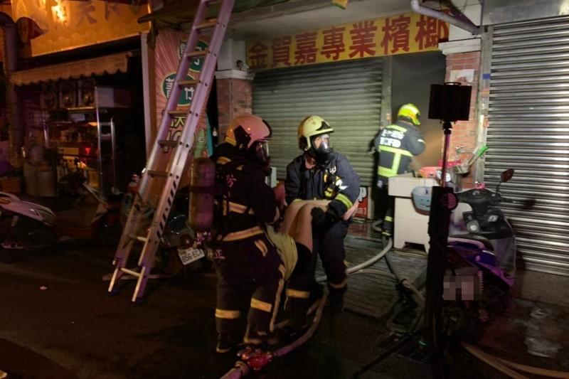 台中太平中山路一間檳榔攤今天凌晨起火,消防人員進入屋內,將在1樓後側房內昏迷的5人陸續救出送醫。(記者陳建志翻攝)