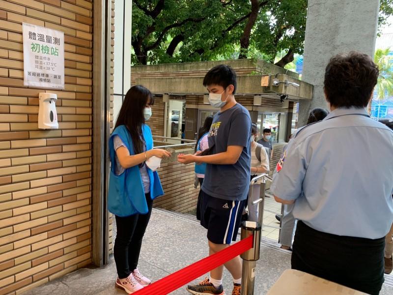 今大學指考碰上武漢肺炎,台北市某考分區學校要求學生消毒後才能入場。(大考中心提供)