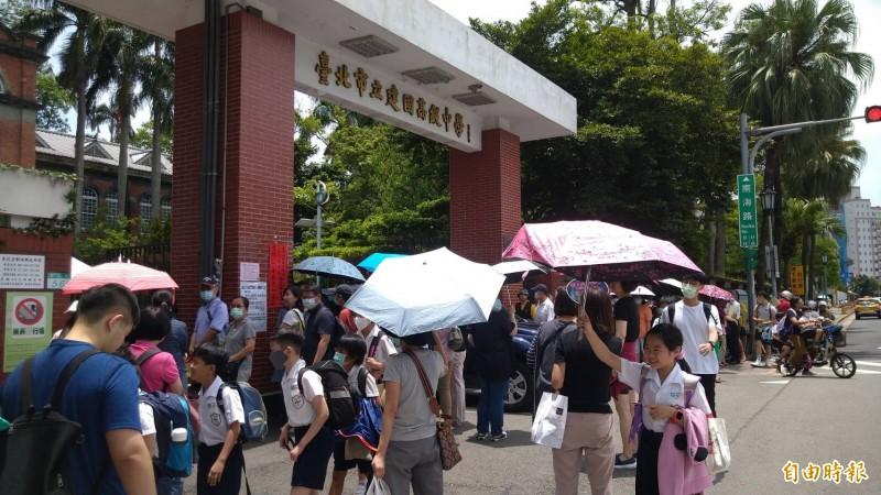 大學指考首日,中午考完試,不少家長頂著烈日站在考場校門口,給考生送便當。(記者蔡亞樺攝)