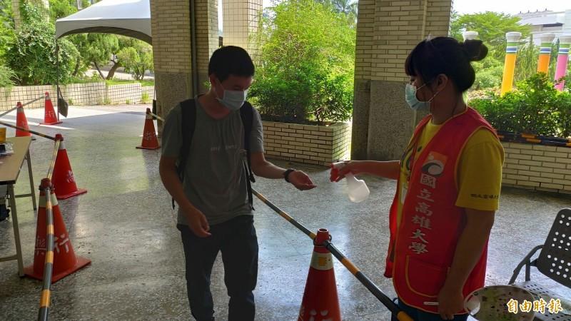 指考下午考英文,圖為高雄大學負責考區消毒情形。(記者黃旭磊攝)