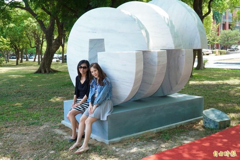 新竹縣府前的新地標「圓通四方」石雕今天亮相,立刻吸引美眉打卡拍照。(記者黃美珠攝)
