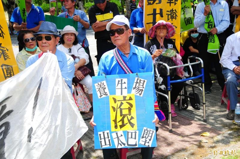 太巴塱部落耆老端坐抗議現場,手拿「養牛場滾出太巴塱」,擔心養牛場污染環境。(記者花孟璟攝)