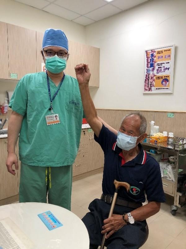 田爺爺(右)開心感謝許惟傑醫師(左)與醫護團隊幫忙治療,讓他的右手能輕鬆舉起超過頭頂、忍不住呵呵笑。(記者王俊忠翻攝)