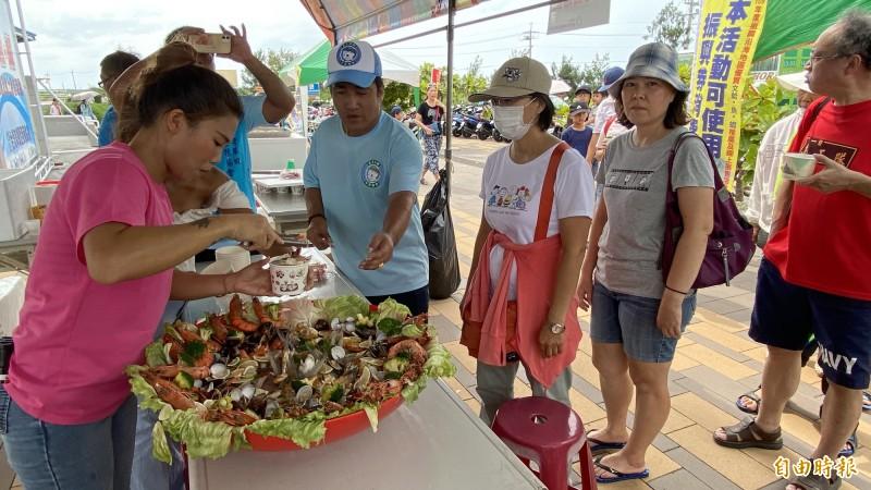 遊客排隊免費試吃海鮮湯。(記者楊金城攝)