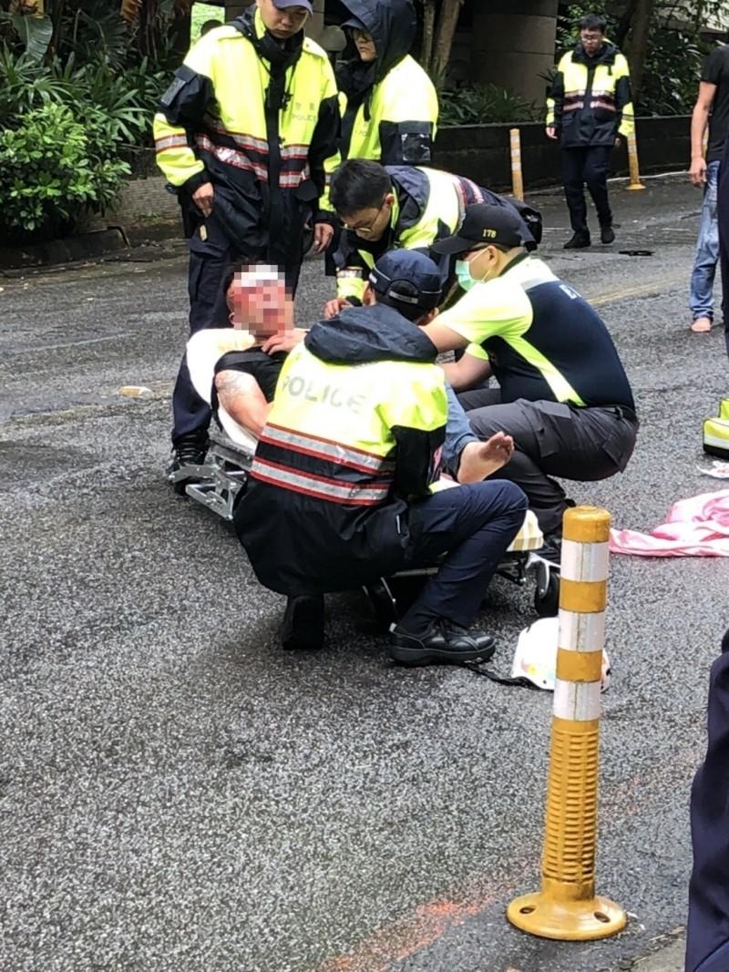 救護人員將滿頭鮮血的黃男抬上擔架送醫救治。(記者吳昇儒翻攝)