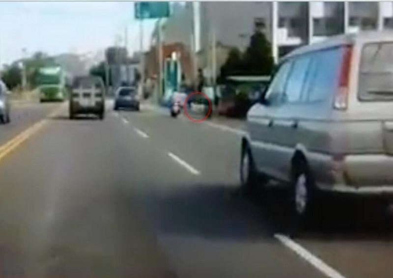 女騎士騎車經過彰化縣社頭鄉員集路段時,路旁一隻小狗(紅圈)突然暴衝到馬路上。(翻攝畫面)