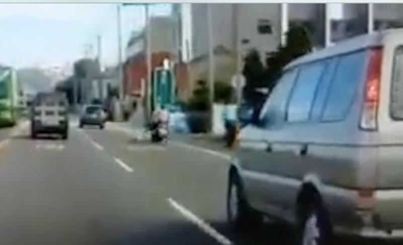 女騎士煞車不及撞上小狗,機車因此失控打滑,後方車輛見狀也緊急煞車閃避。(翻攝畫面)