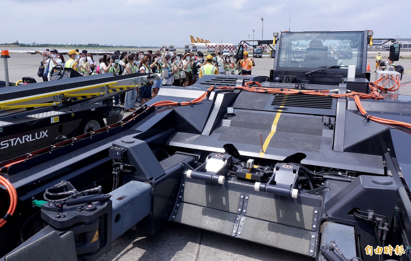 星宇航空特別安排旅客搭乘Link Monster接駁車到遠機坪登機,並且派地勤人員介紹停在飛機旁的勤務車。(記者朱沛雄攝)