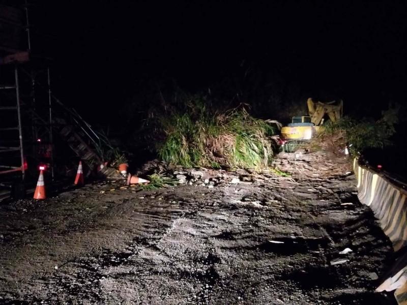 台20線栗園段昨晚無預警坍方,施工包商動員怪手清除障礙。(記者陳賢義翻攝)