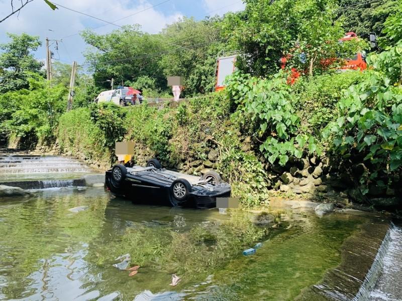 黑色小客車4輪朝天翻落高雄美濃的水底溪。(記者許麗娟翻攝)