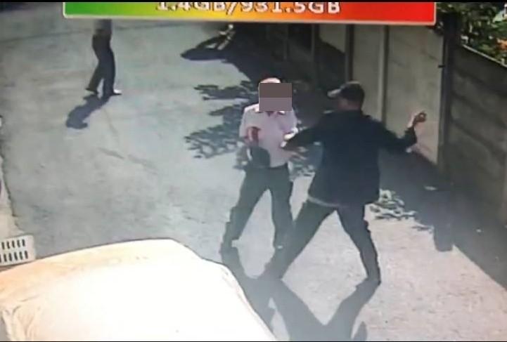 吳男(戴帽者)持玻璃碎片不斷攻擊父親,父親襯衫胸前血跡斑斑,不斷求饒仍被刺。(記者陳冠備翻攝)